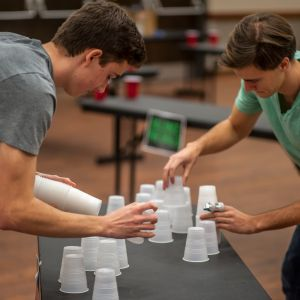 Two male students compete in a cup stacking contest during the Live Action Game Night.
