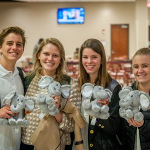 Three female students and a male student pose with elephant stuffed animals that they created at the Do-It-Yourself event.