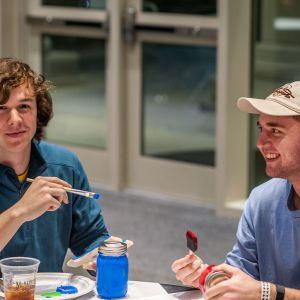 Two male students paint mason jars at the Do-It-Yourself event. One student smiles into the camera as the other student laughs.