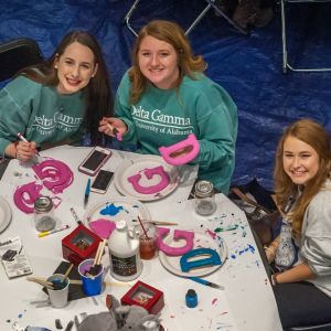 Three female students smile into the camera while painting letter decorations at the Do-It-Yourself event.