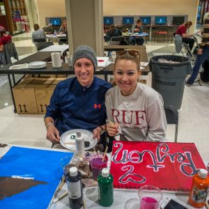 A male student and a female student smile for the camera while painting canvases during the Do-It-Yourself event.
