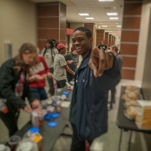 A male student laughs and points at the camera during the Do-It-Yourself event.