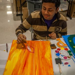 A male student smiles as he paints a canvas with orange paint during the Do-It-Yourself event.