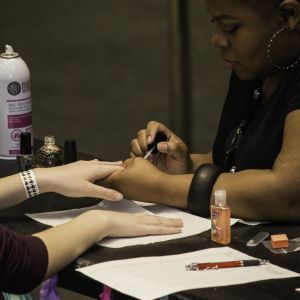 Pictured is a female painting the nails of another female during the Battle of the Sexes event.