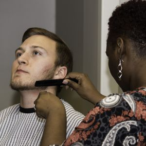 A female trims the beard of a male student at the Battle of the Sexes.