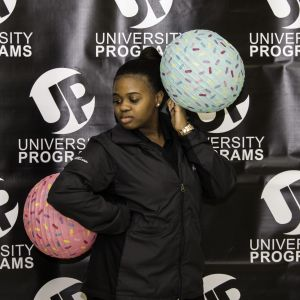 A female student poses in front of a University Programs backdrop. She is holding balloons with sprinkles printed on them and posing for the camera.