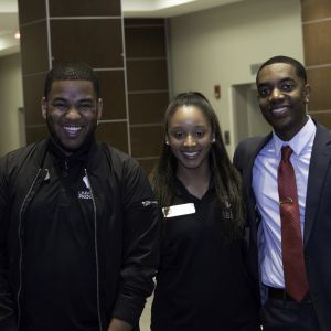 Two male students and a female student are smiling into the camera.