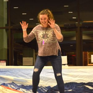 A female student attempts the snowboarding simulator at the Winter Welcome Bash. She has her hands in the air and she is smiling.