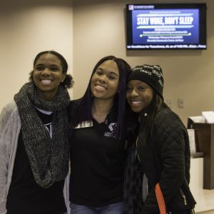 Three female students huddle together and smile for the camera.