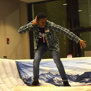 A male student attempts the snowboarding simulator at the Winter Welcome Bash. He is posing for the camera.