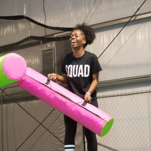 A female student laughs as she and a friend joust at the UpSurge Excursion Event.