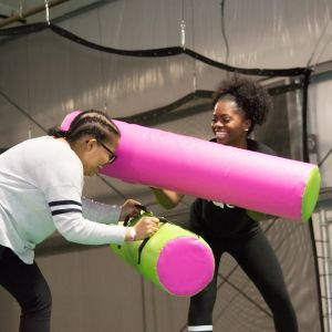 Two female students joust each other and laugh at the UpSurge Excursion event.