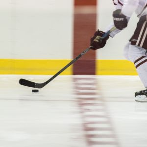 An Alabama hockey player slides a hockey puck on the ice.