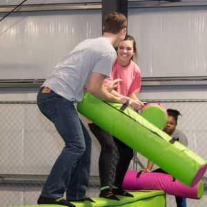 A male student and a female student joust each other at the UpSurge Excursion event.