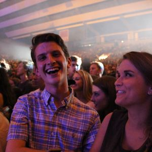 A man in a button down shirt smiles for the camera, a woman to his left looks at him with a smile. The Welcome Back Concert is in the background