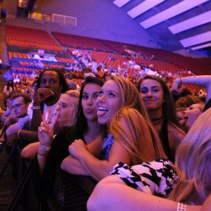 Two girls are leaning over a black barrier keeping the crowd away from the stage at the Welcome Back Concert. One is making a kiss-face at the camera and the other is sticking her tongue out. The Welcome Back Concert is in the background