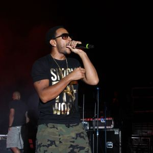 A man (Ludacris) holds a microphone up to his mouth on a stage in Coleman Coliseum