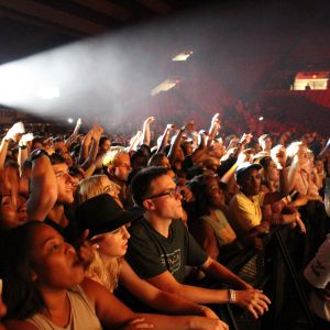 A crowd of students leans over the black barrier separating them from the stage in Coleman Coliseum. They are illuminated by the light of the stage