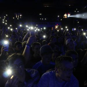 A crowd of students in Welcome Back Concert hold their phone lights up to the camera in a darkened Coleman Coliseum