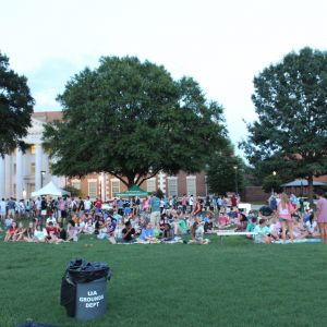 Pictured is a crowd of students sitting down on the quad, most of them are on blankets on the grass. There are a few standing tents in the background