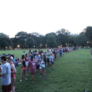 Pictured is a group of students lined up on the quad at around dusk. Most of them are conversing or using their phones