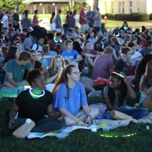 Pictured is a large crowd of students sitting on the grass of the quad on blankets. Many of them are wearing glow in the dark accessories