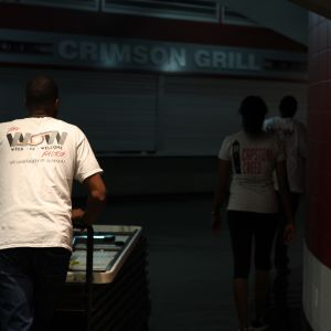 Three students are seen from the back wearing Week Of Welcome shirts.