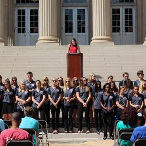 Pictured is SGA President Lillian Roth at a podium in front of the Gorgas Library. In front of her is a group of students in grey short-sleeved collared shirts.