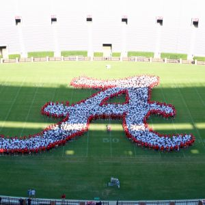 Pictured is the Alabama Script A formed by students in red and white t-shirts on the Bryant Denny Football Stadium Green